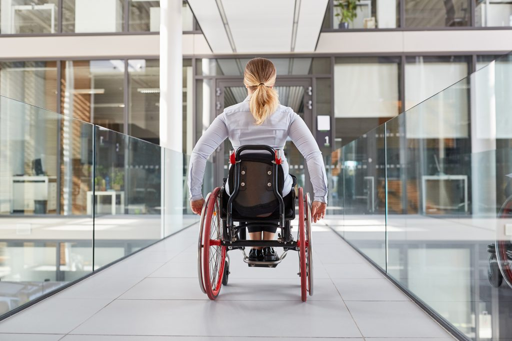 אישה בכסא גלגלים על גשר בתוך בניין